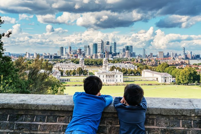 Photo of two kids leaning against a low wall looking at a city and urban landscape from a distance.